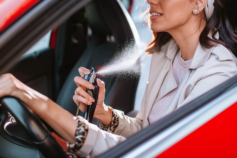 mujer usando perfume en un auto rojo